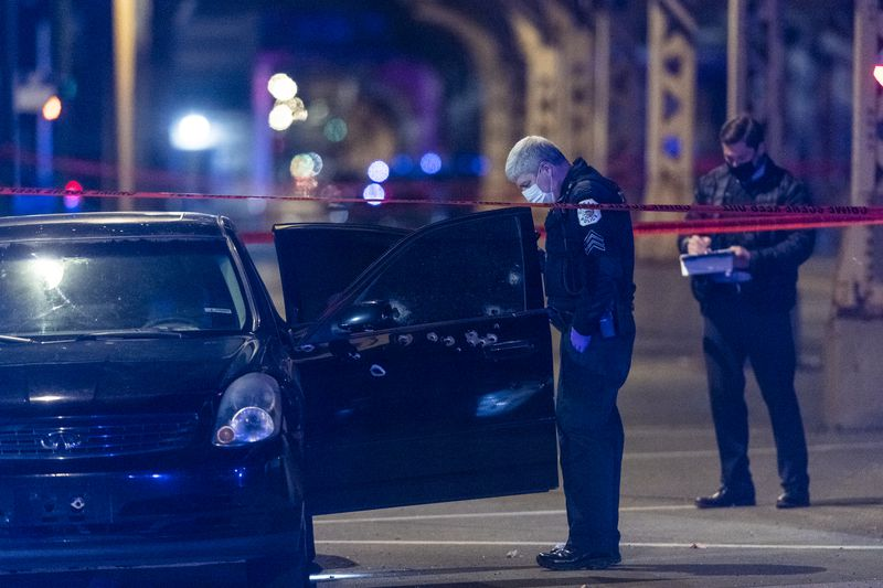 Chicago police investigate the scene where three people were shot, including a 10-year-old boy in the 3100 block of West Lake St. in the East Garfield Park neighborhood, Friday, March 19, 2021.