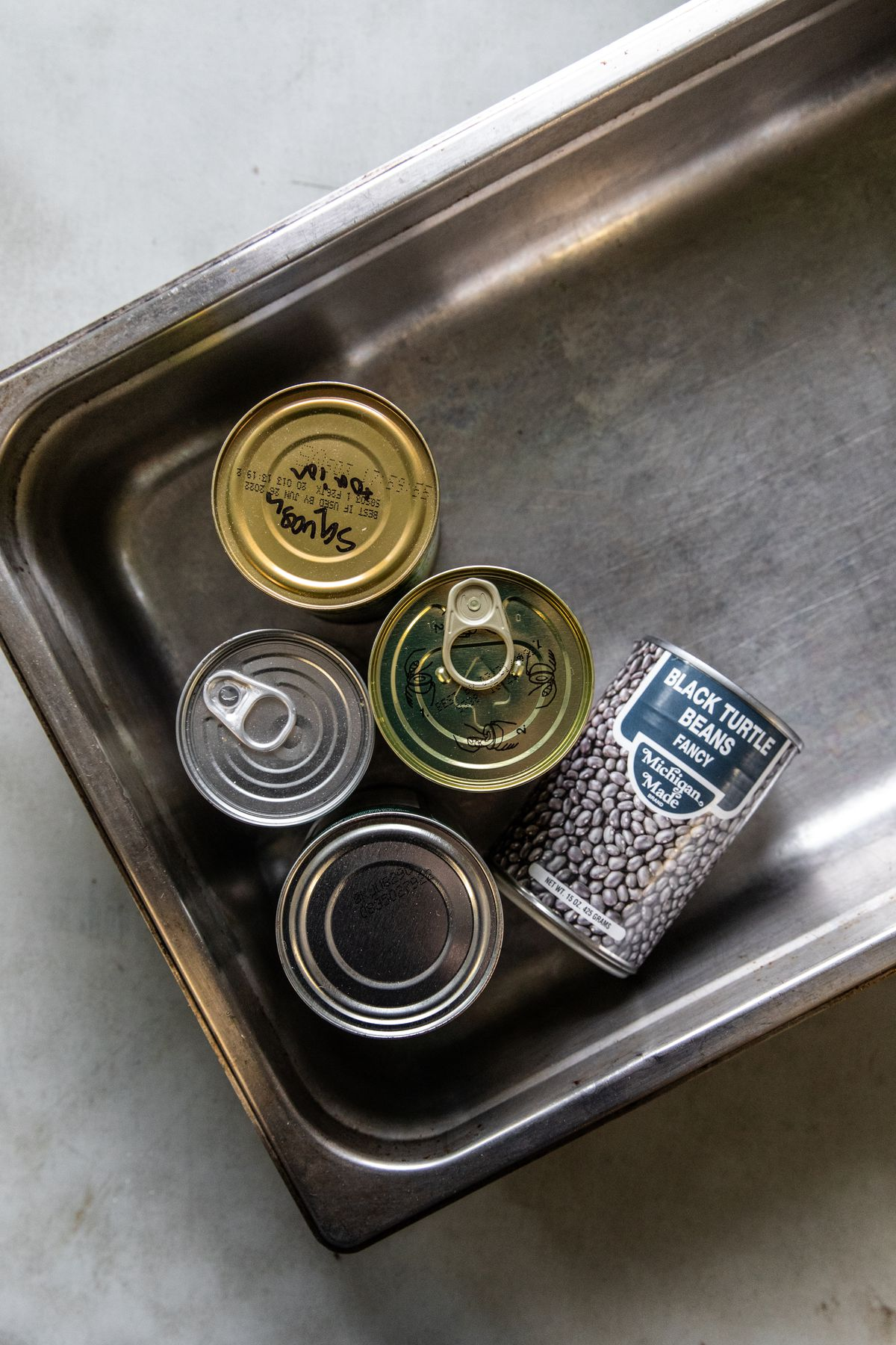 A collection of canned goods in a steel pan