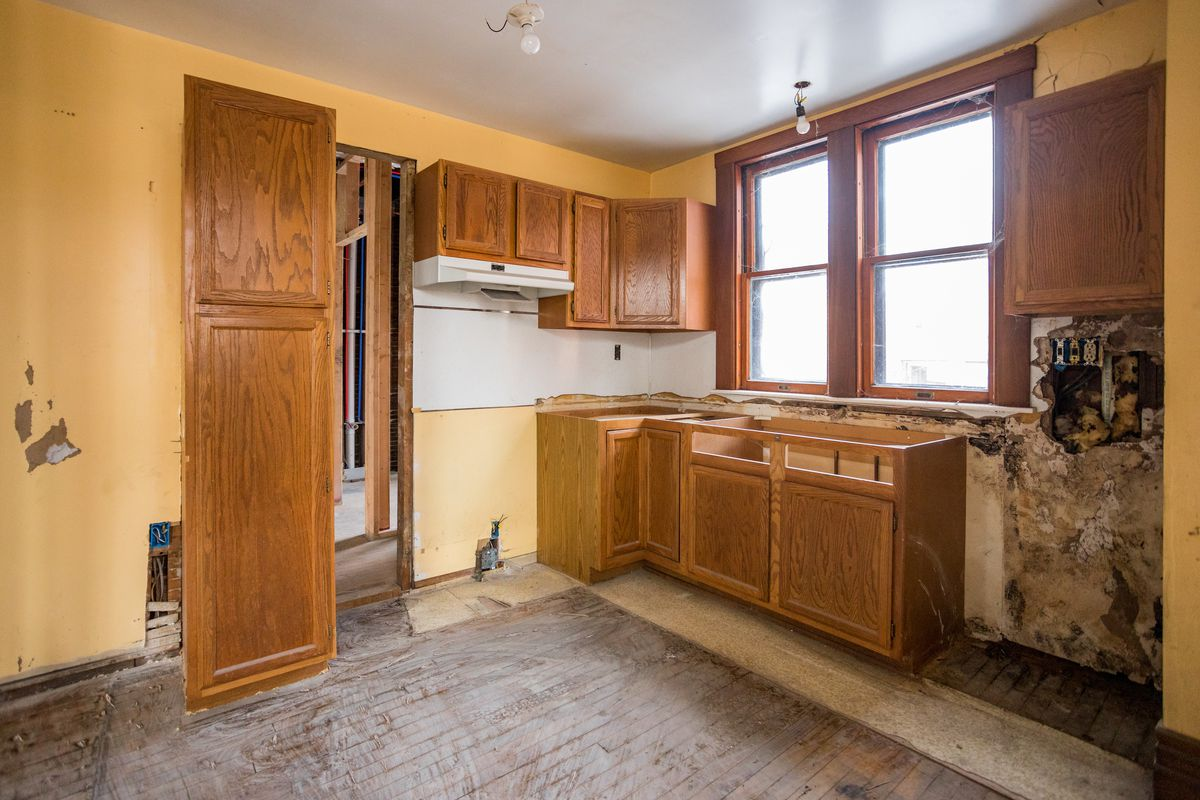 A kitchen with just cabinets. Some of the walls look moldy and there's no tiles on the floor.