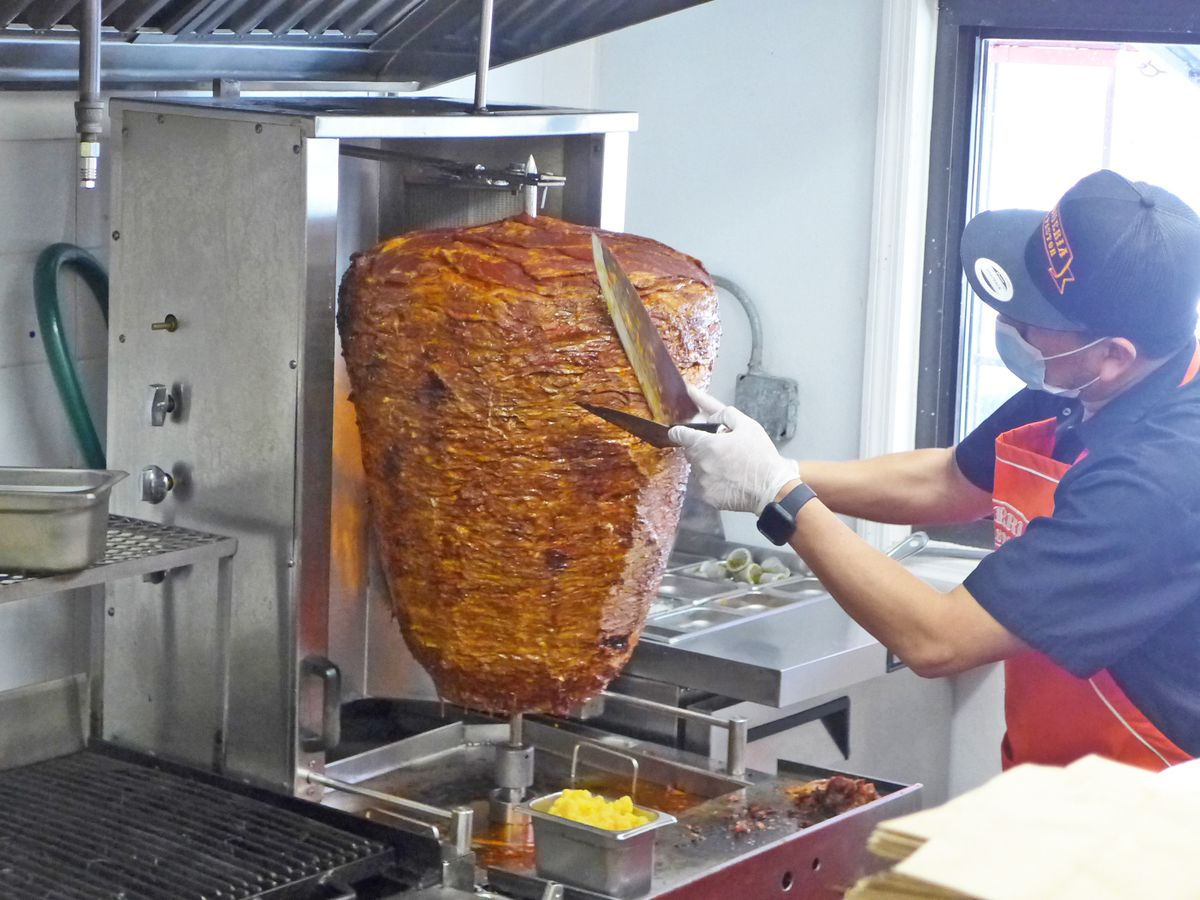 A man in a blue shirt with a long knife bends over a twirling vertical spit of meat.