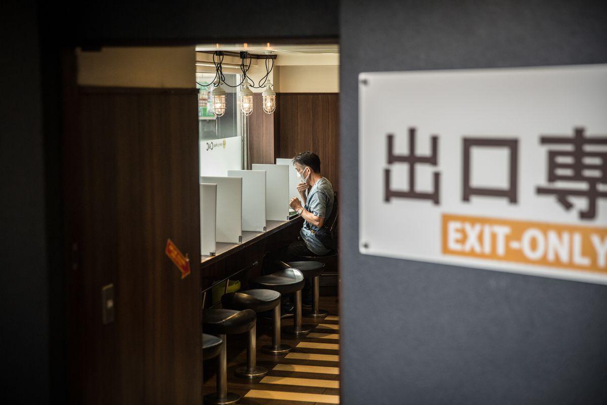 man sits in at a counter to eat that has small dividing walls between stools.