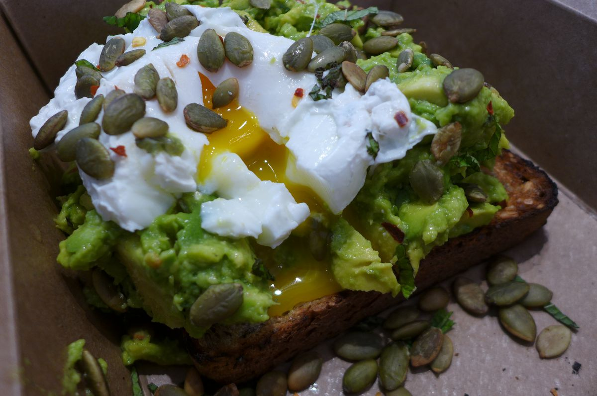 Avocado toast stopped with a poached egg and sunflower seeds
