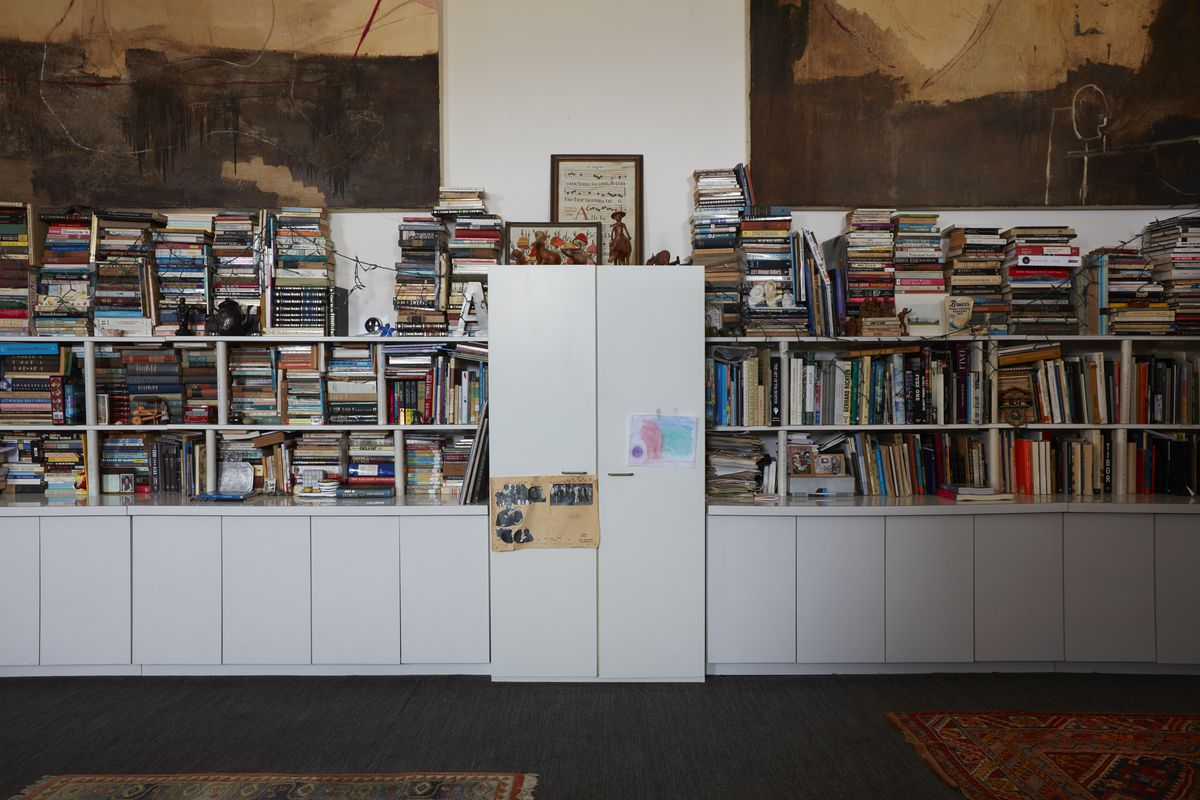 Simple white shelves are stacked high with books.