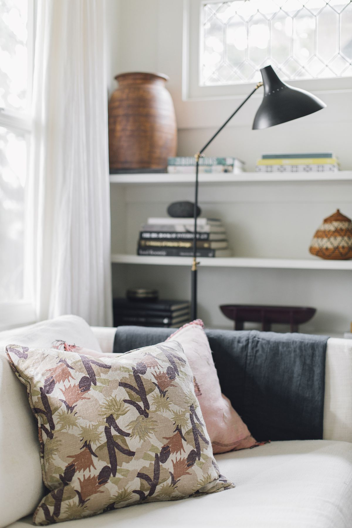 The corner of a living room. There is a couch that is white with multiple assorted pillows. There is a black floor-lamp. There are shelves with various objects.