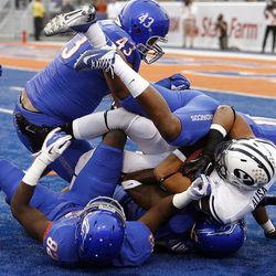 Michael Alisa (42) of the Brigham Young Cougars is tackled by Boise State defenders during NCAA football in Boise, Thursday, Sept. 20, 2012.