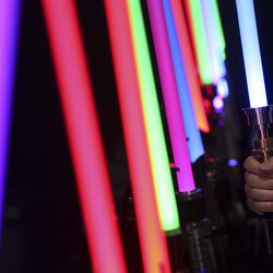 A FanX attendee examines a lightsaber at a booth during the first day of FanX at the Salt Palace Convention Center in Salt Lake City on Thursday, Sept. 5, 2019.