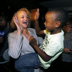 Jackie Biskupski holds her son, Archie, as she reacts to reports that she is ahead in the mayoral race in Salt Lake City during her election night party in Sugar House on Tuesday, Nov. 3, 2015.