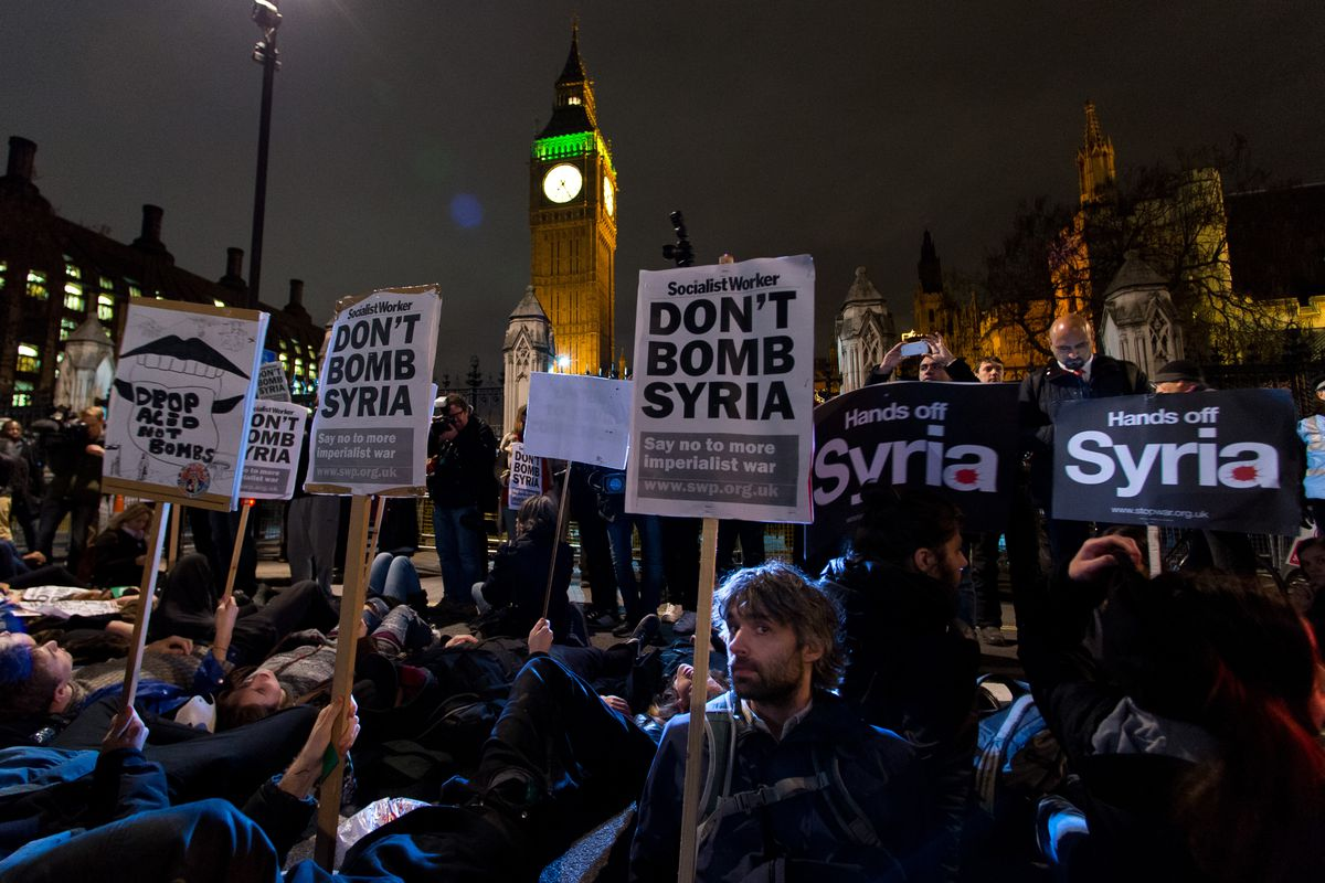 """Protesters participate in a """"die in"""" protest in Parliament Square on December 2, 2015, in London, England, in advance of a vote in the House of Commons on whether to carry out airstrikes against ISIS in Syria."""