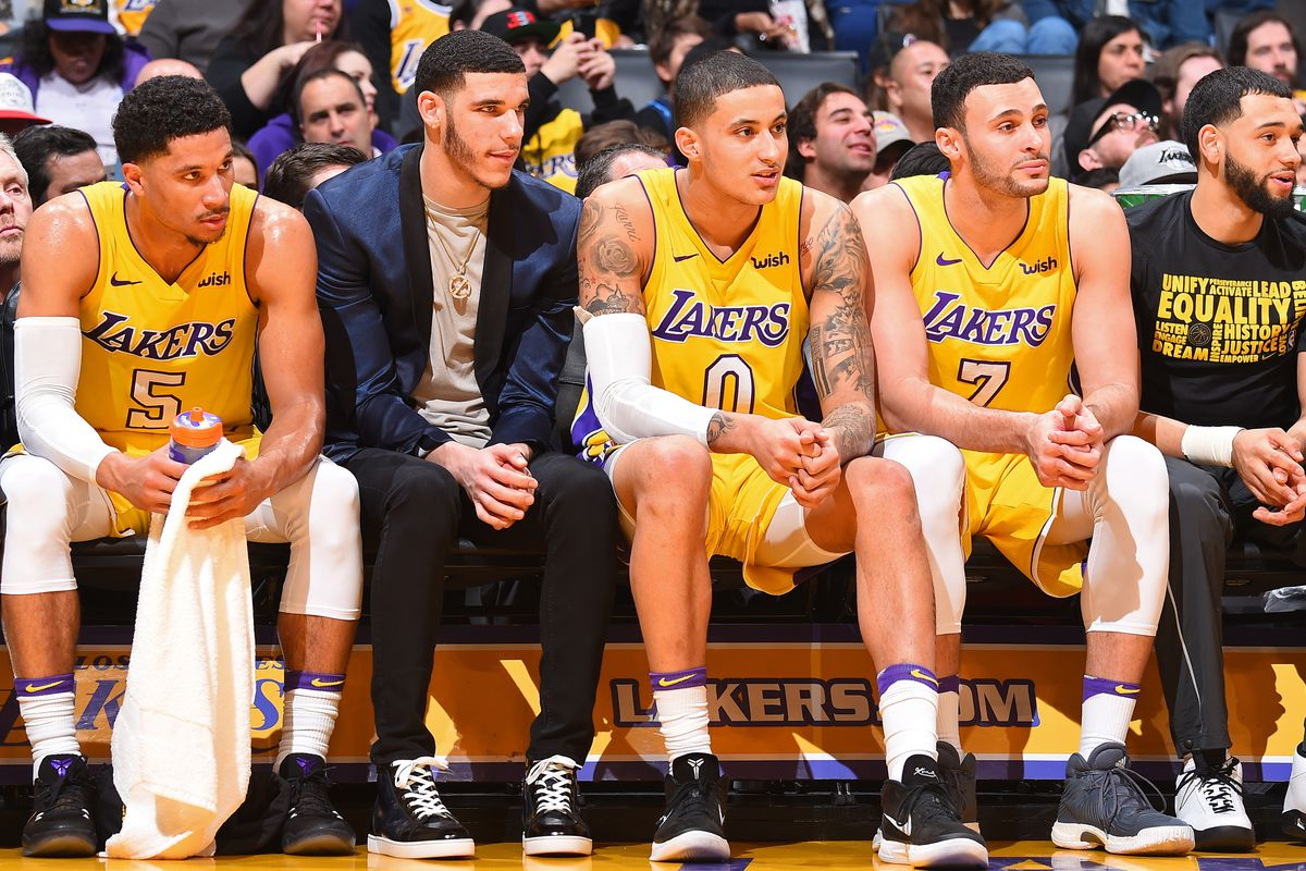LA Lakers players sit on the sideline of a basketball game. The Wish logo is on their jerseys.