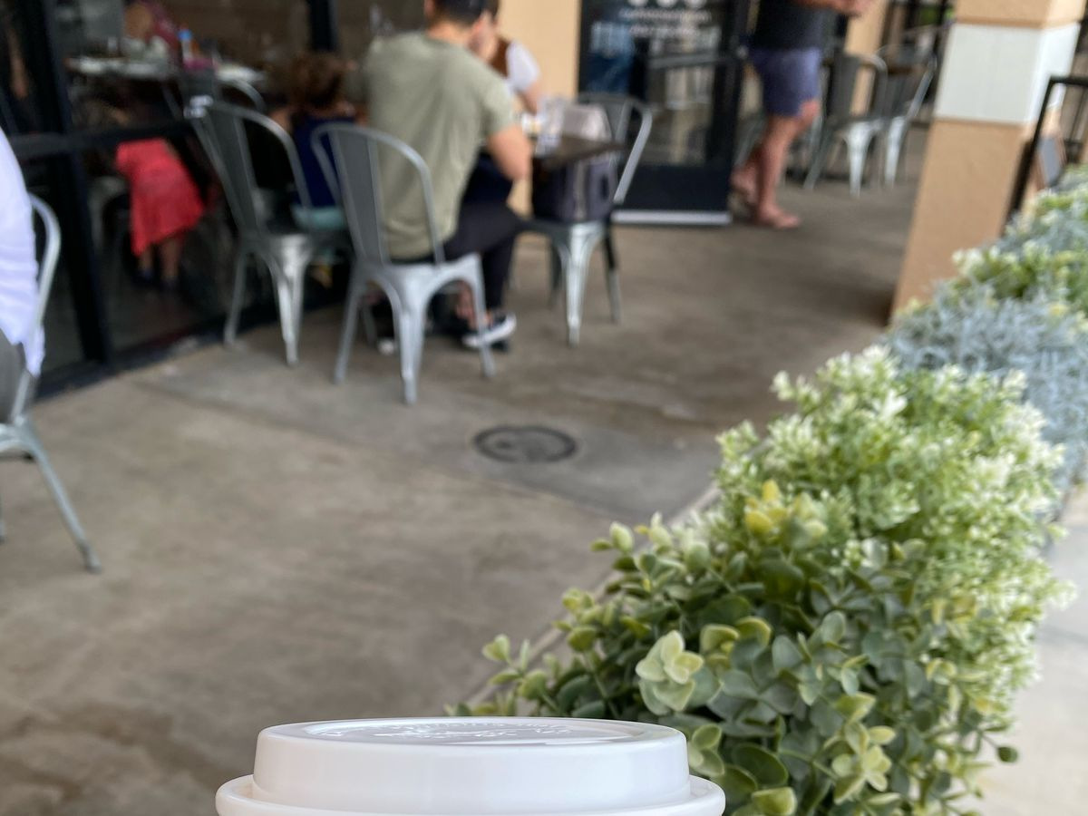 A small patio with a coffee cup in the foreground
