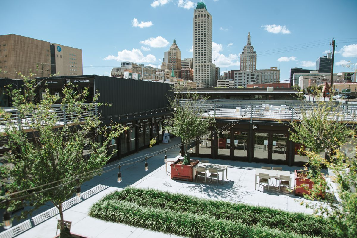 A sunny day with a grass and cement courtyard in the foreground. String lights run overhead, and there are young trees scattered around. Two sets of tables and chairs sit in the courtyard. In the background, a city skyline is visible.