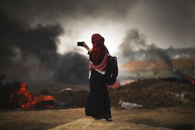 A Palestinian woman documents the situation at the border fence with Israel as mass demonstrations continue on May 14, 2018.