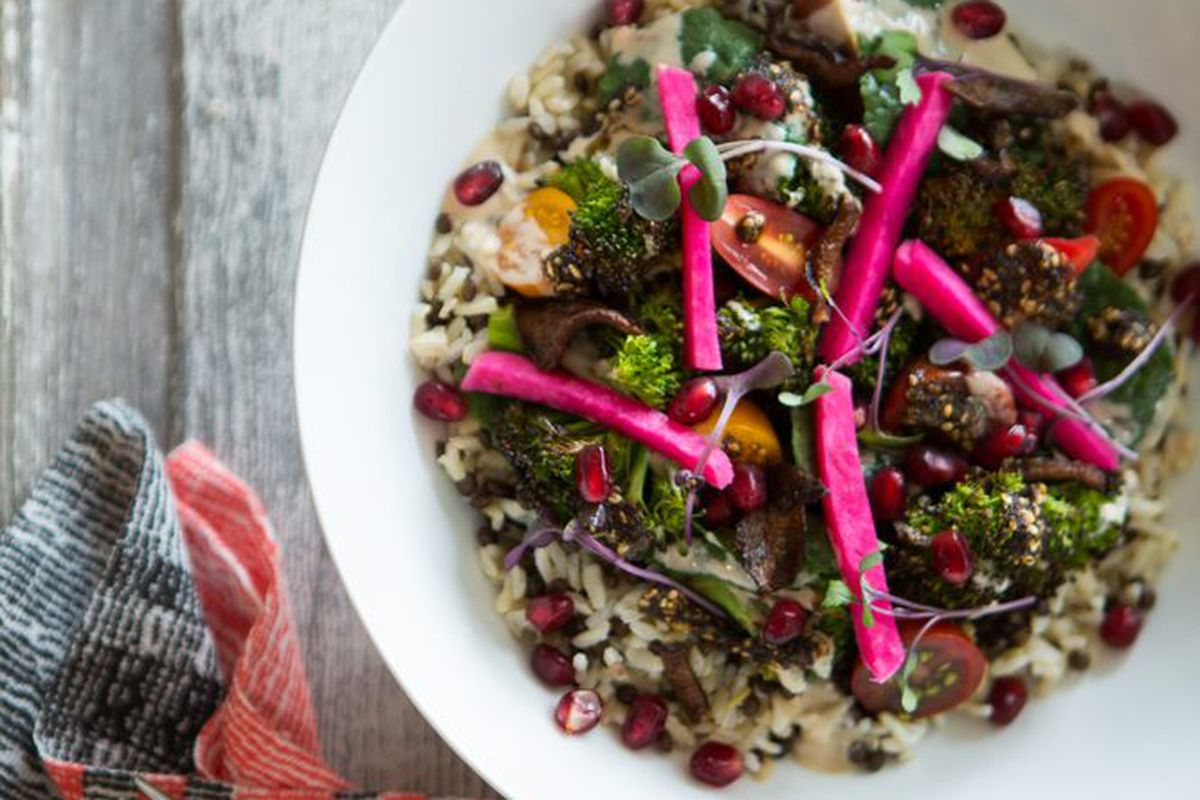 A vegan grain bowl with pomegranate seeds, broccoli, and more