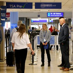 Maddie Frommelt, CLEAR ambassador, greets travelers during the launch of a new biometric, fee-based service that allows travelers to move past manual ID verification lines using fingerprints and iris scans, at the Salt Lake City International Airport in Salt Lake City on Wednesday, July 12, 2017.
