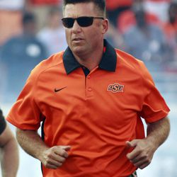 Oklahoma State head coach Mike Gundy runs onto the field before the start of an NCAA college football game against Savannah State in Stillwater, Okla., Saturday, Sept. 1, 2012.