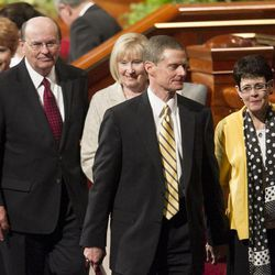 Elder Quentin L. Cook of the Quorum of the Twelve Apostles and his wife Mary and Elder David A. Bednar and his wife Susan walk off the stand after the afternoon session Saturday, April 6, 2013 of the 183th Annual General Conference of The Church of Jesus Christ of Latter-day Saints in the Conference Center.