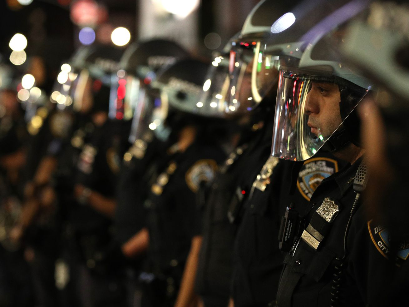 Police officers lined up wearing face shields
