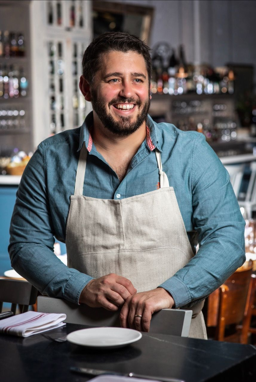 Headshot of chef Will Gilson. He is wearing a light blue button-down shirt under a beige linen apron and looking to the side while smiling. The interior of restaurant is visible in the background of the photo.