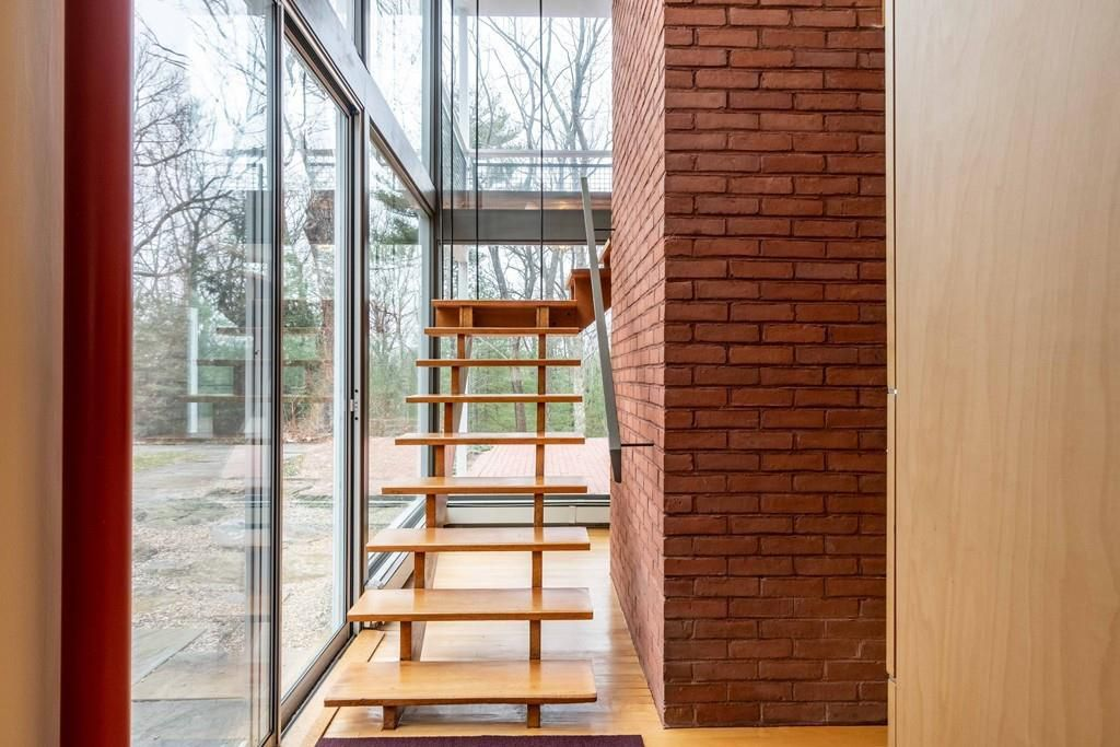 A floating staircase next to very large windows.