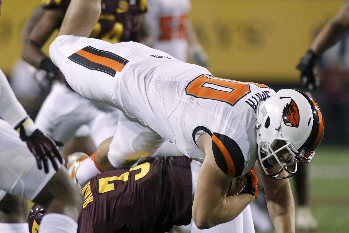 Tight end Caleb Smith #10 of the Oregon State Beavers is up-ended by defensive back Damarious Randall #3 of the Arizona State Sun Devils