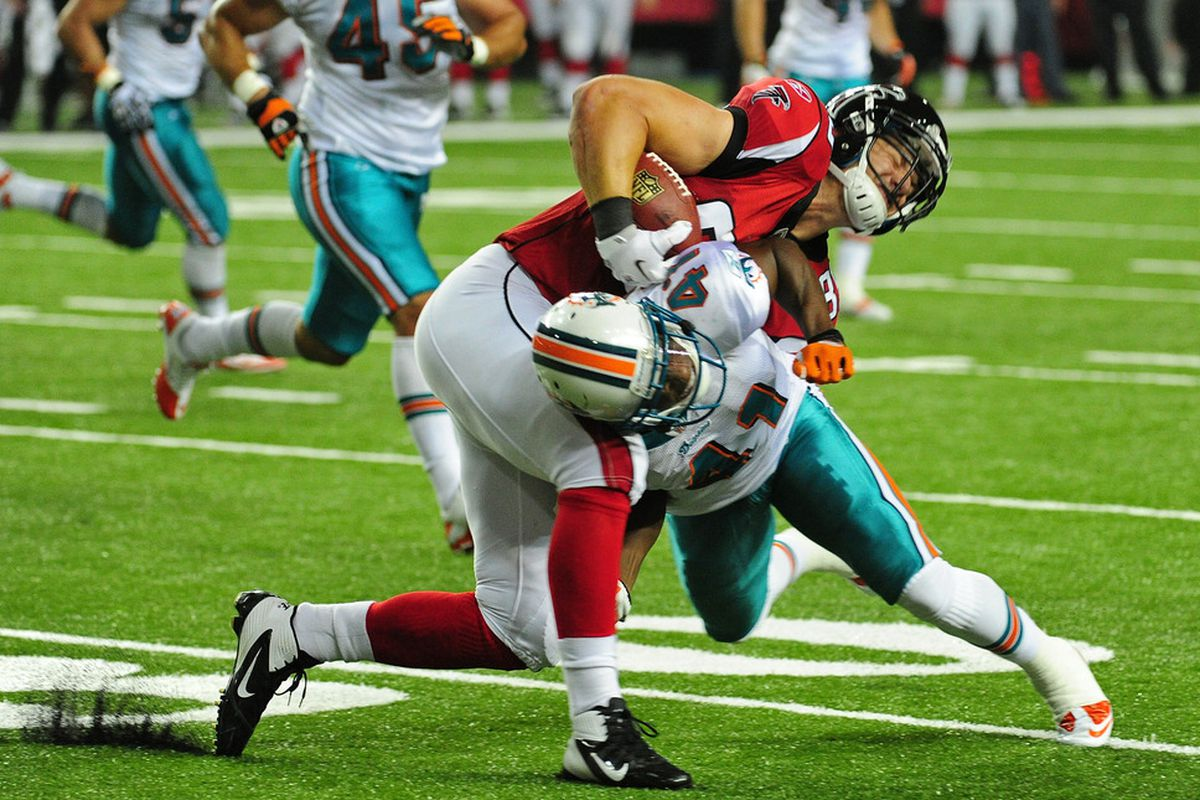 ATLANTA - AUGUST 12:  Ryan Winterswyk #86 of the Atlanta Falcons is tackle by Vincent Agnew #41 of the Miami Dolphins during a preseason game at the Georgia Dome on August 12, 2011 in Atlanta, Georgia. (Photo by Scott Cunningham/Getty Images)