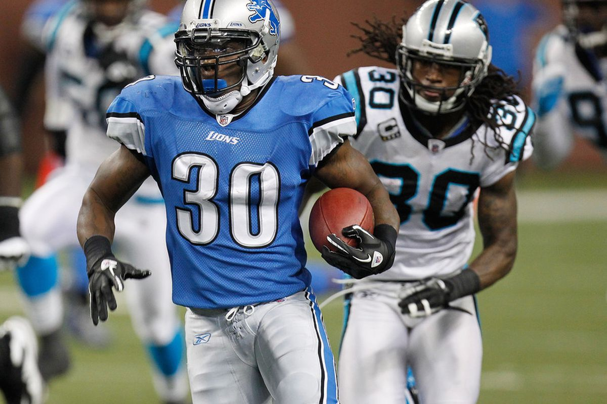 DETROIT, MI - NOVEMBER 20:  Kevin Smith #30 of the Detroit Lions look for running room in front of Charles Godfrey #30 of the Carolina Panthers at Ford Field on November 20, 2011 in Detroit, Michigan.  (Photo by Gregory Shamus/Getty Images)
