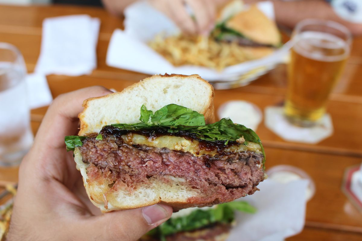 The famed father's office burger on a big bun with arugula.