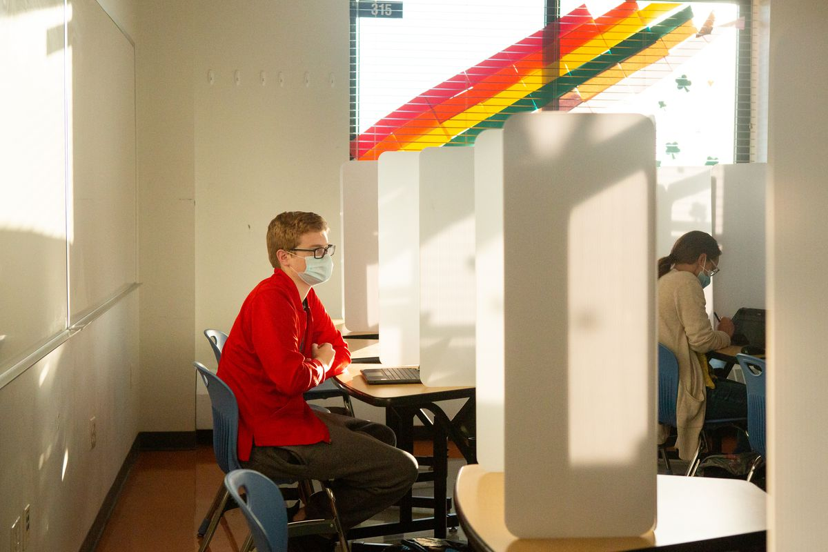 A masked teacher with glasses, wearing a red shirt and brown slacks, looks at a laptop as she sits at a desk separated by a folding white partition from the row in front where another person sits.