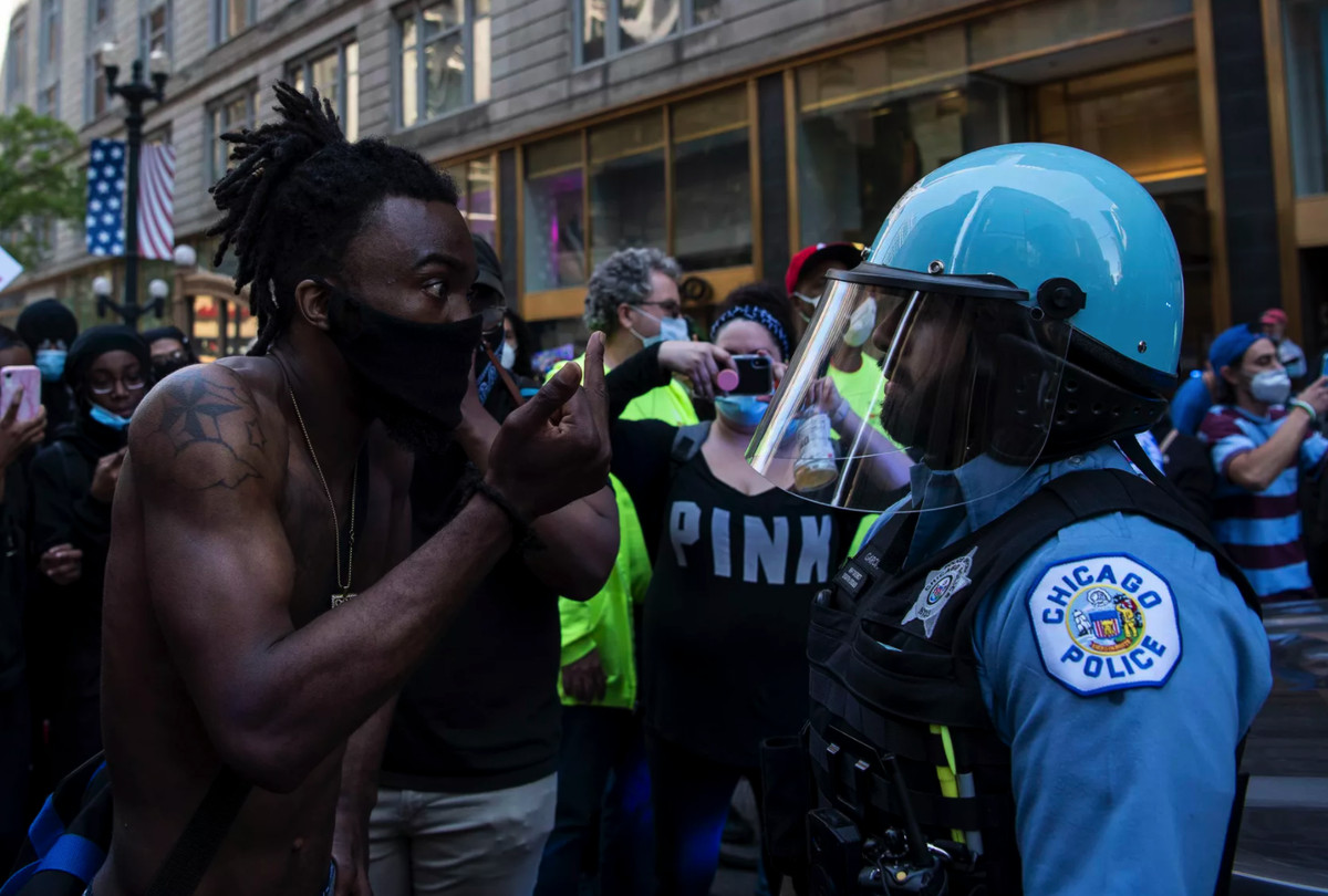 A protester gives a Chicago police officer the finger during last summer's protests in the Loop.