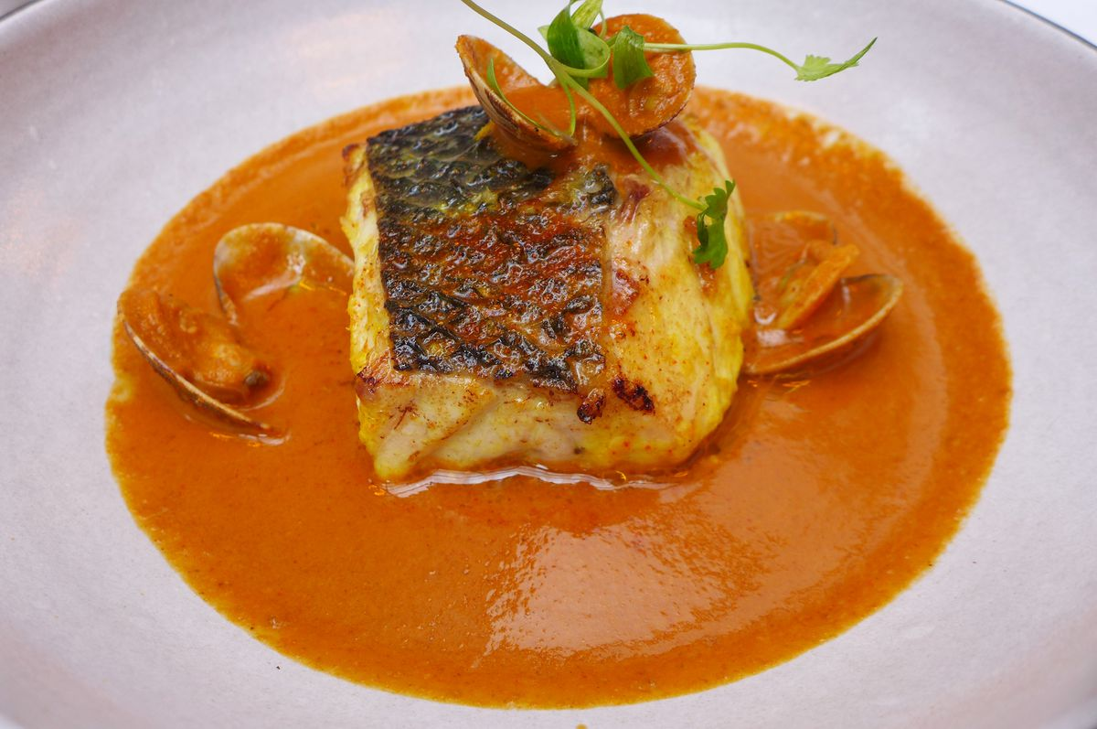 A skin on fish filet rests in a thick orange sauce.