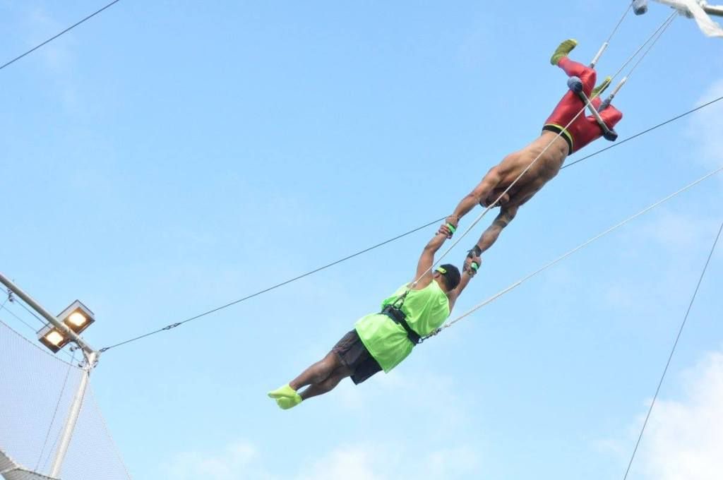 A pair of trapezists hang on to each other in the air