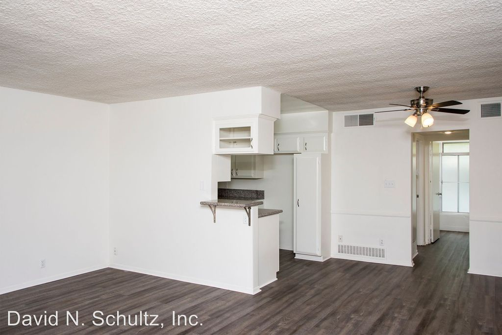 A living room with gray floors looking into a kitchen