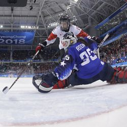 Melodie Daoust (15), of Canada, scores a goal against goalie Maddie Rooney (35), of the United States, in the penalty shootout.