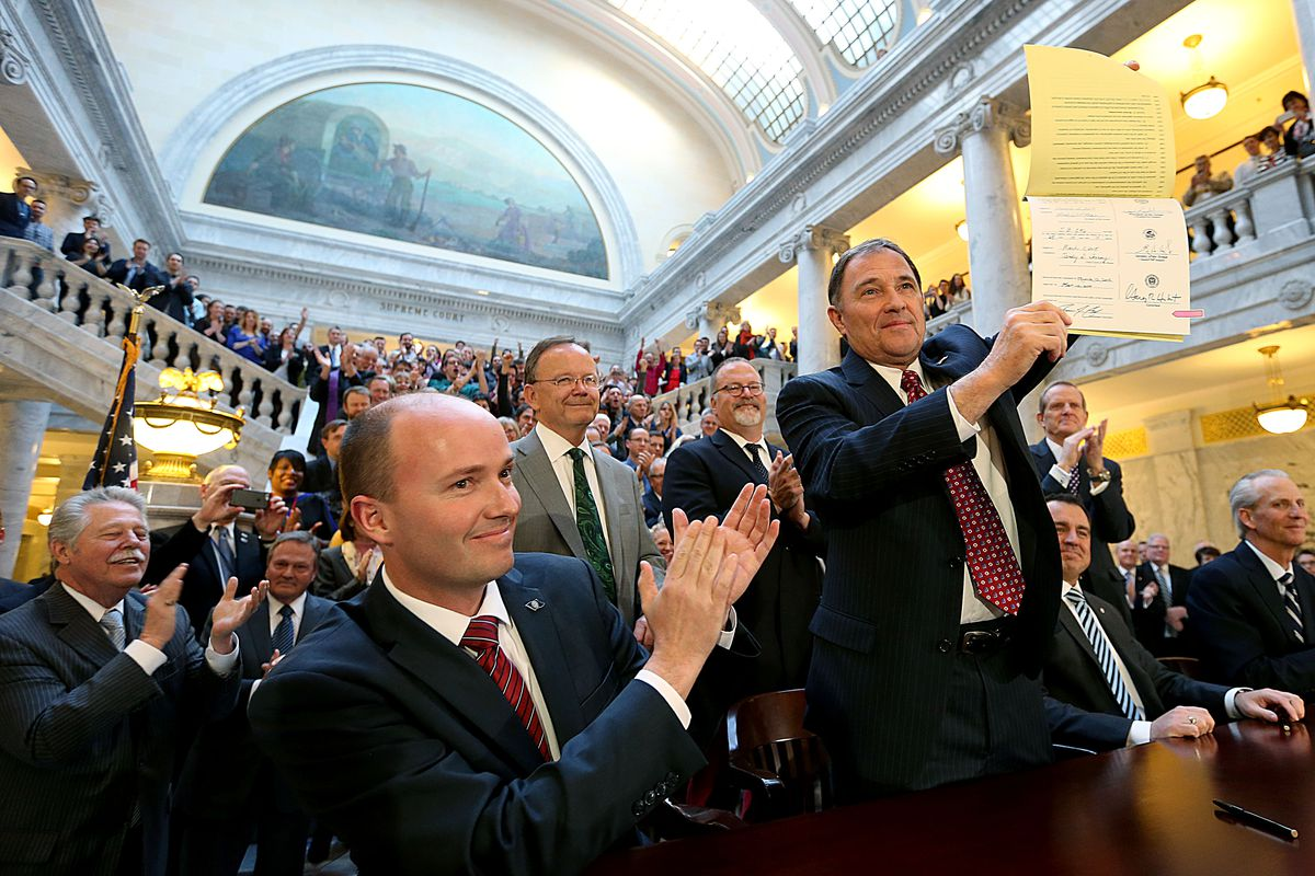 Governor Gary Herbert holds up a copy of Senate Bill 296 Antidiscrimination and Religious Freedom Amendments after signing it at the Capitol in Salt Lake City on Thursday, March 12, 2015.