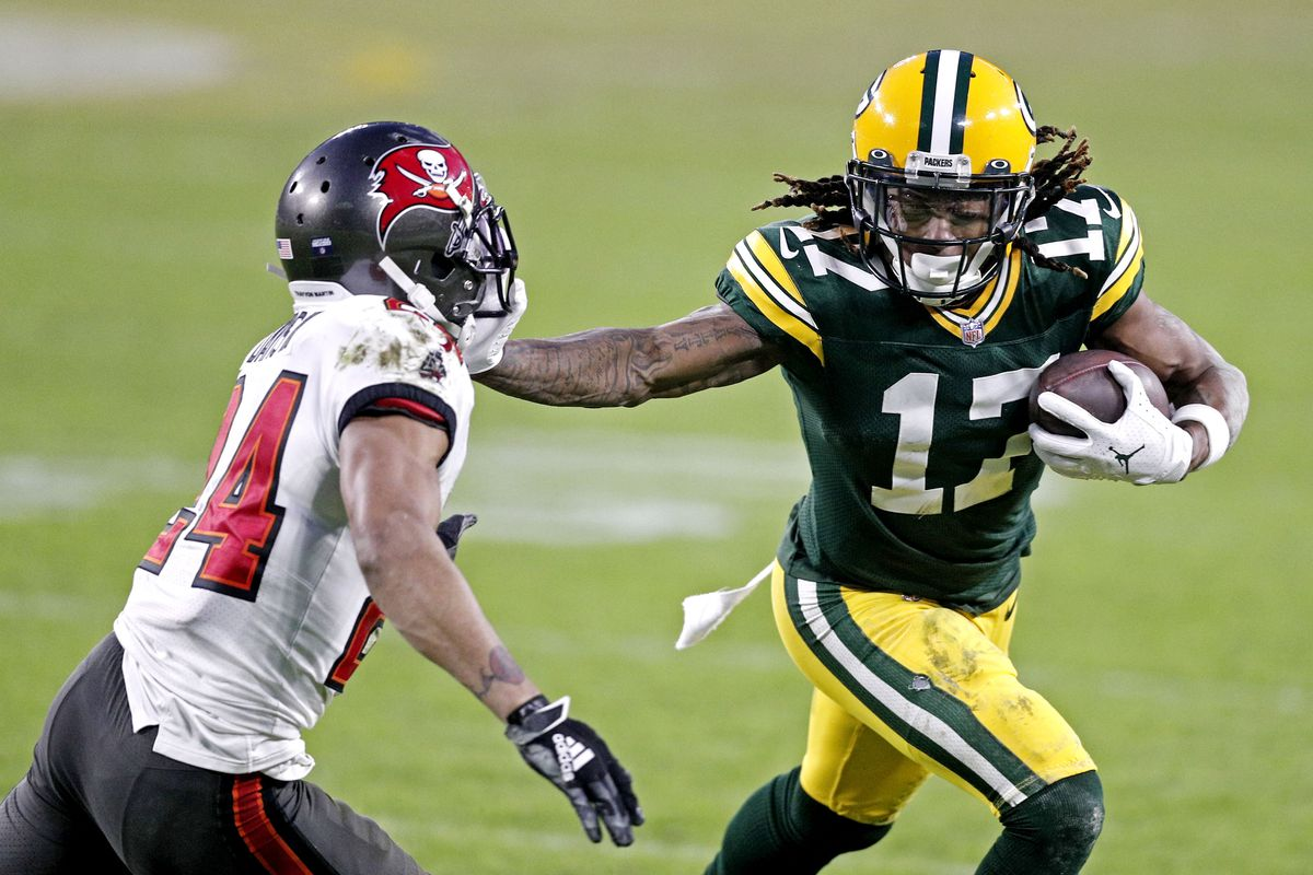 Green Bay Packers wide receiver Davante Adams (17) runs the ball against Tampa Bay Buccaneers cornerback Carlton Davis (24) during the fourth quarter in the NFC Championship Game at Lambeau Field.