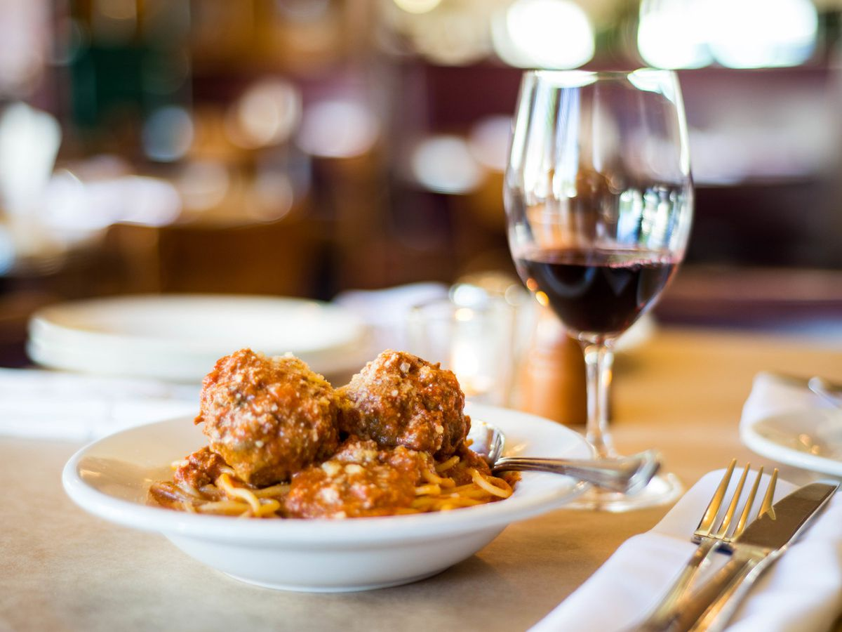 Plate of spaghetti beside glass of red wine