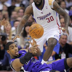 Sacramento Kings center Jason Thompson, bottom, passes the ball from the floor as Los Angeles Clippers forward Reggie Evans watches during the first half of their NBA basketball game, Saturday, April 7, 2012, in Los Angeles.