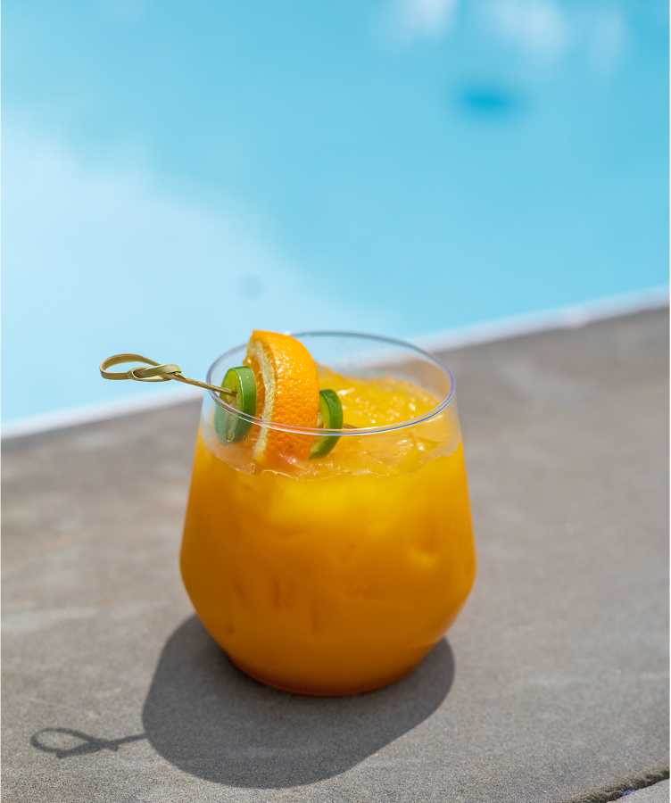A bright orange cocktail with a skewer of jalapeno slices and orange