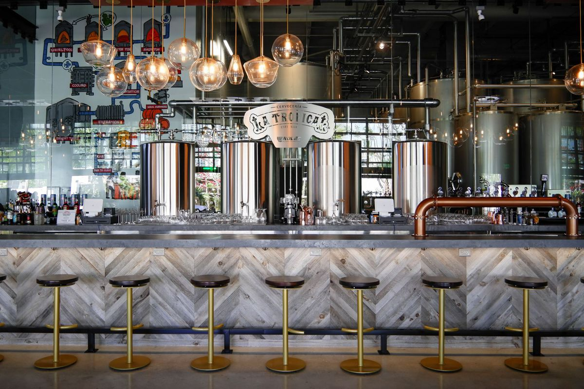 Large gray bar with golden plated stools in front and taproom in back