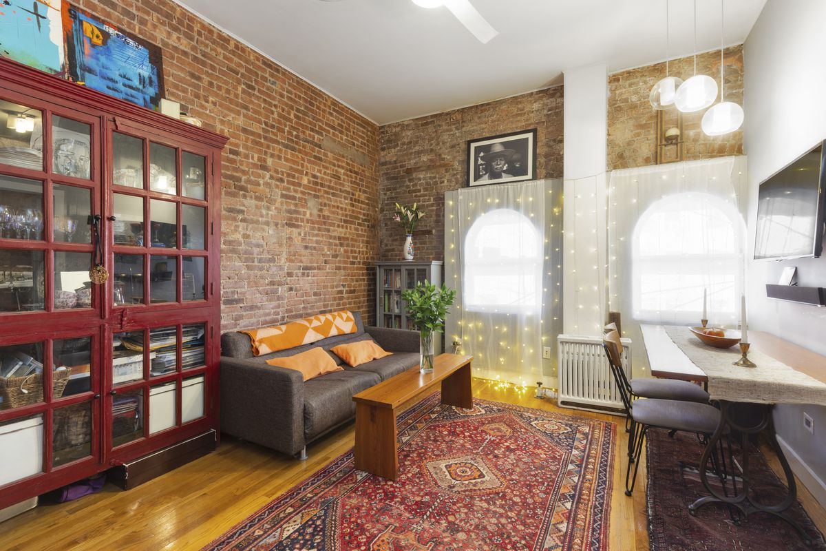 A living area with exposed brick, a brown couch, a rug, and two arched windows.