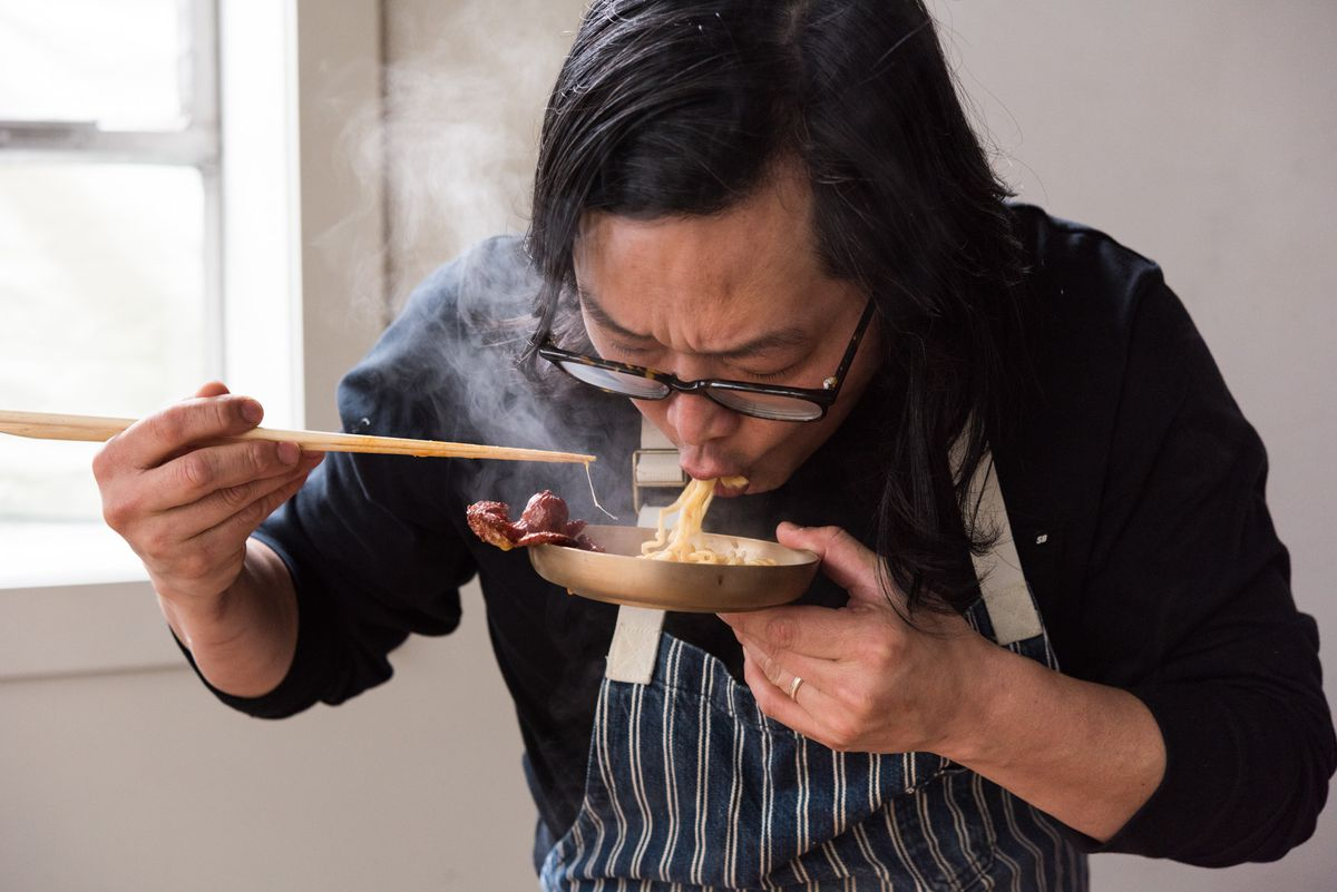 Peter Cho slurps noodles from a bowl, chopsticks pointing at his mouth. He's wearing an apron, and steam fogs up his glasses.
