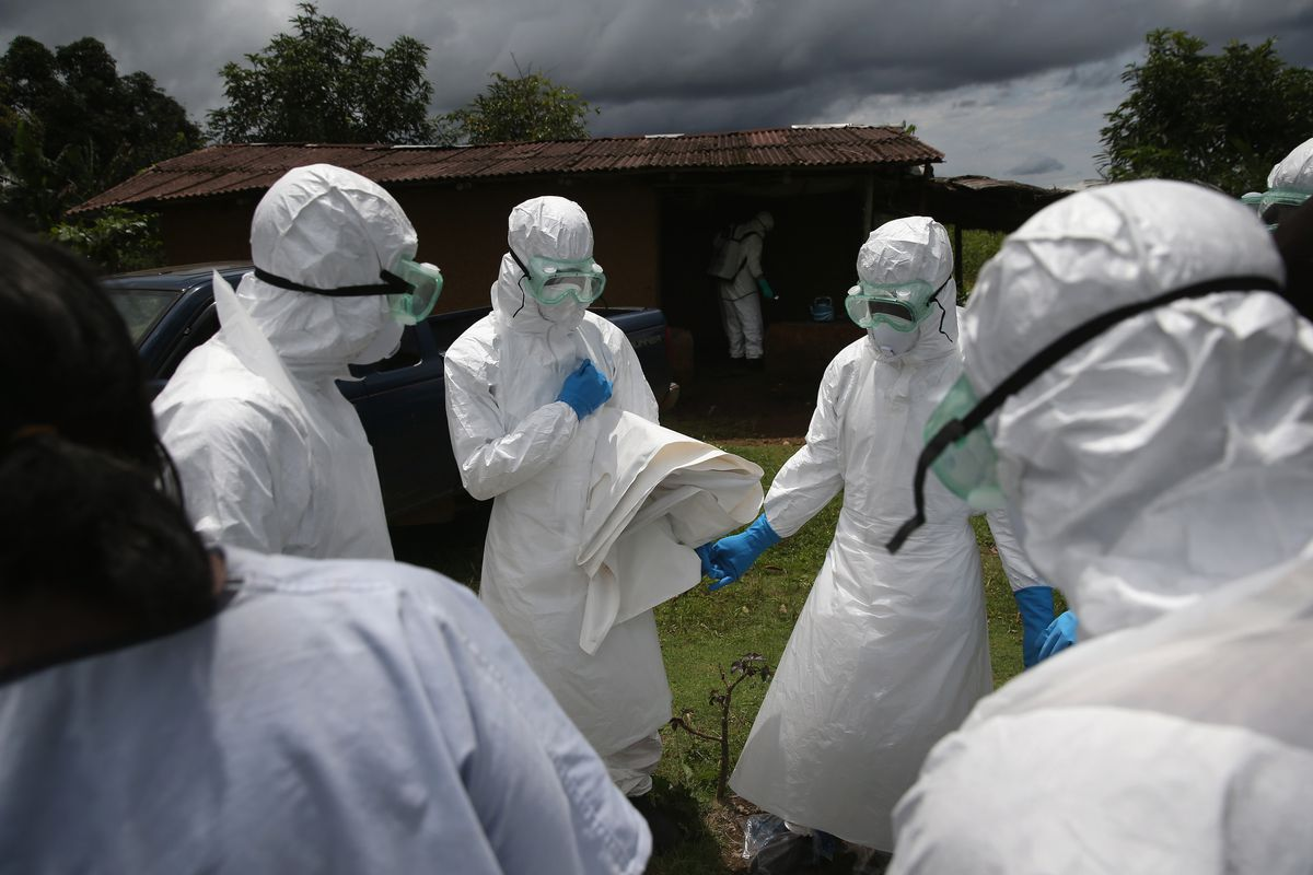 A burial team from the Liberian Red Cross prays before collecting the body of an Ebola victim near Monrovia, Liberia.