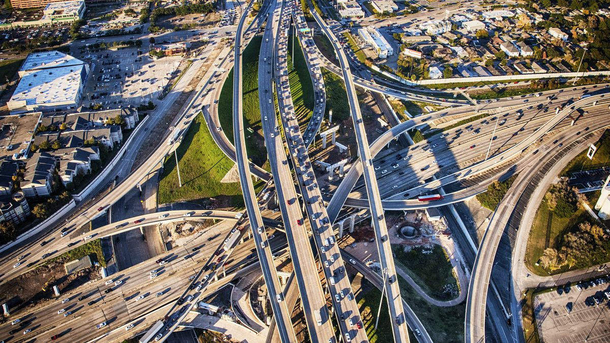 Two giant interstates with at least eight lanes each intersect as shadows stretch in the early evening light as seen from overhead.