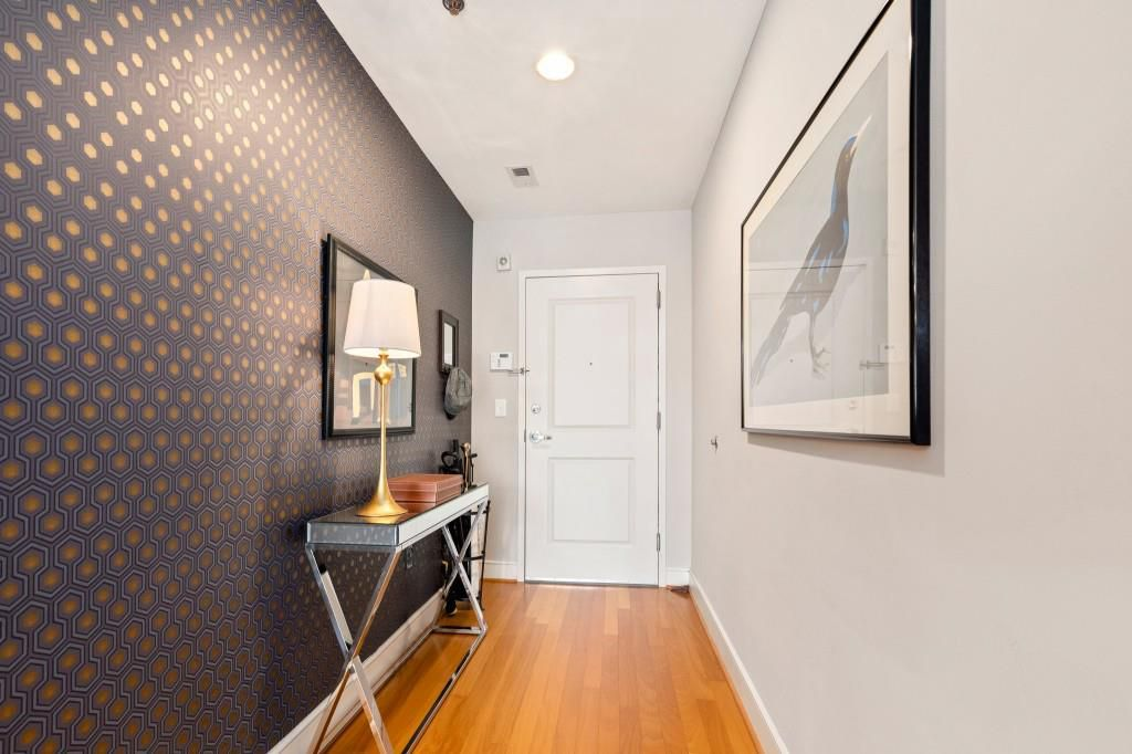 The entry of a condo with a white wall at right and wallpapered wall at left.