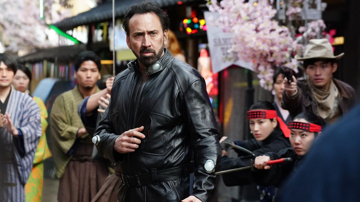 Nicolas Cage in a leather suit preparing to karate chop someone as a crowd watches in Prisoners of the Ghostland