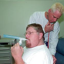 Respiratory therapist Todd Wuergler, right, treats Bret Rees for breathing problems at an Orem hospital.