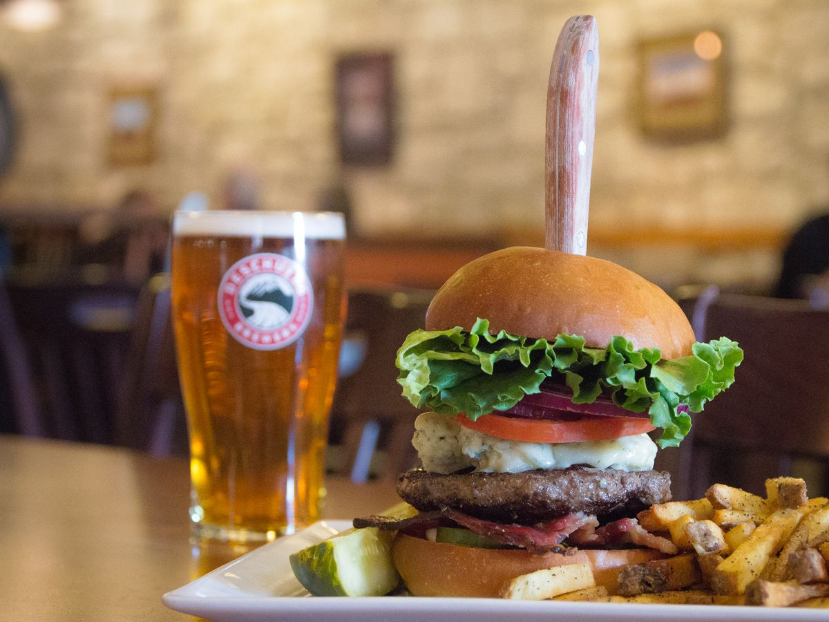 A picture of an amber-colored beer in a glass; a tall burger with lettuce, onion, tomato, and blue cheese; and a pile of fries at Deschutes