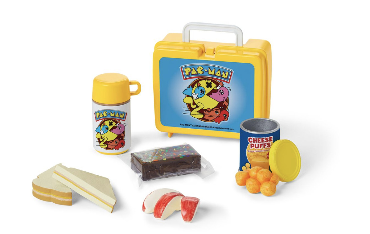 A doll-sized lunchbox set with a Pac-Man thermos, sandwich, brownie, apple slices, and container of cheese balls.