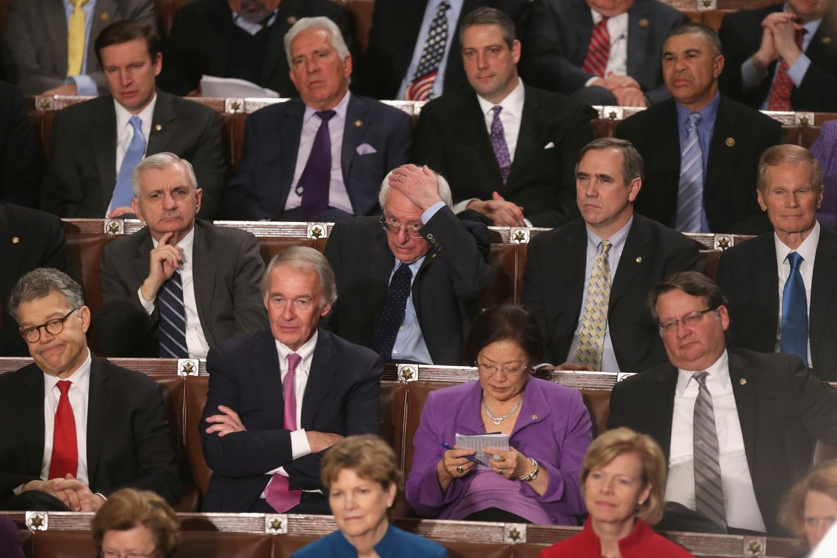 Members of Congress including US Sen. Bernie Sanders (I-VT) (C) listen to US President Barack Obama deliver the State of the Union speech in the House chamber of the US Capitol January 12, 2016, in Washington, DC.