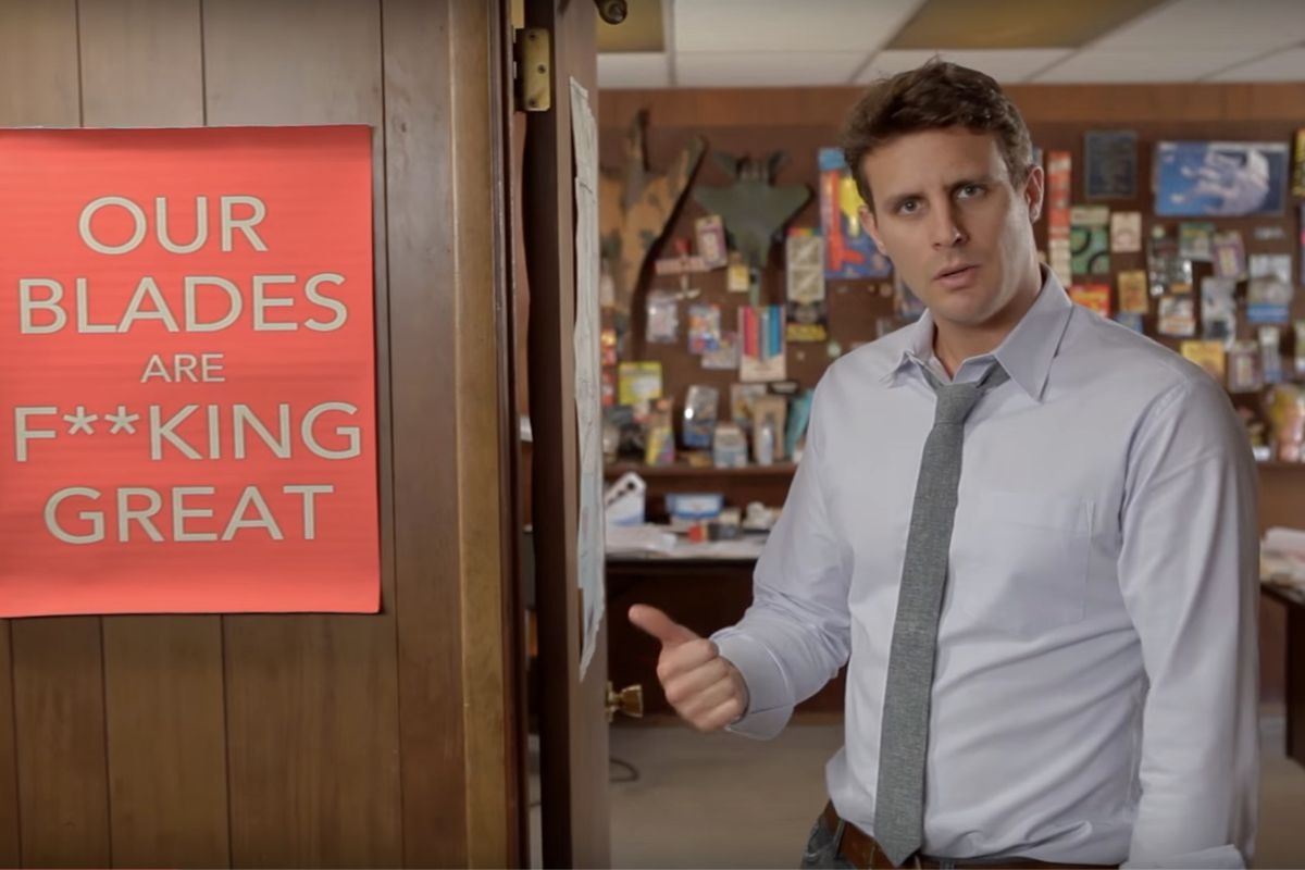 """Image of Dollar Shave Club's CEO, Michael Dubin, from a promotional video next to a sign that says """"our blades are f**king great"""""""